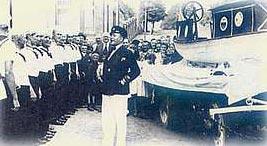 """1934: Taufe der ersten """"Pinass Brumse"""" im Heimathafen, vor der Stadtschänke. Kapitän Ingenol (Günther Gedat) mit seiner Matrosen-Mannschaft."""